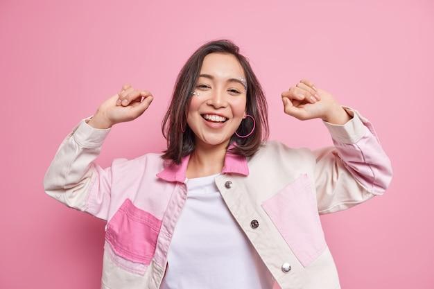 인생을 즐기고 있습니다. 긍정적 인 아름다운 아시아 밀레 니얼 소녀는 재미 있고 분홍색 벽 위에 고립 된 세련된 재킷을 입은 평온한 미소를 춤추며 좋아하는 노래로 이동합니다.