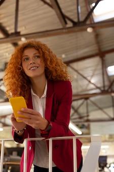 少し休憩を楽しんでいます。黄色いスマートフォンを立って、仕事から少し休憩を楽しんでいる巻き毛の女性