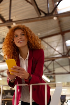 Enjoying little break. curly woman holding yellow smartphone standing and enjoying little break from work