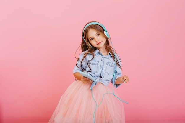 Enjoying lovely music through blue head[hones of cute little girl with long brunette hair isolated on pink background. fashionable child in tulle skirt expressing true positive emotions to camera