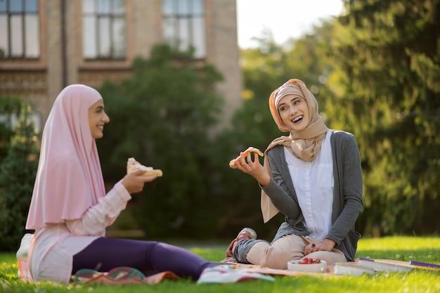 점심 시간을 즐기고 있습니다. 히잡을 입고 웃고 피자를 먹고 점심 시간을 즐기는 무슬림 학생들