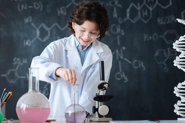 현대 실험을 즐기고 있습니다. 실험실에 서서 과학 프로젝트에 참여하는 동안 화학 수업을 즐기는 쾌활한 미소 능력 아이