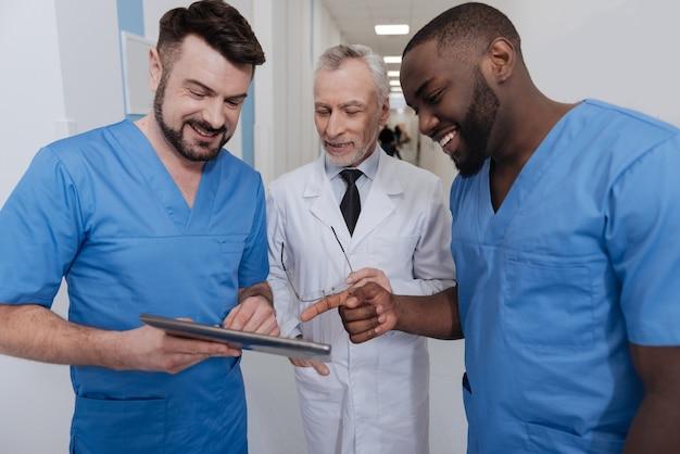 現代のテクノロジーを一緒に楽しむ。病院に立って、現代のタブレットを使用しながら会話を楽しんでいるうれしそうなフレンドリーな笑顔の開業医