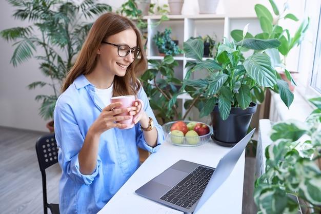 Наслаждаясь утренним кофе счастливая бизнес-леди молодая женщина-фрилансер в очках, сидя за столом и