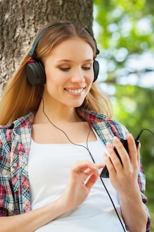 음악과 신선한 공기를 즐깁니다. 헤드폰을 끼고 음악을 들으며 공원에 있는 나무에 기대어 웃고 있는 아름다운 젊은 여성