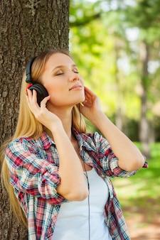 음악과 신선한 공기를 즐깁니다. 헤드폰을 끼고 공원에서 나무에 기대어 음악을 듣고 웃고 있는 아름다운 젊은 여성의 측면