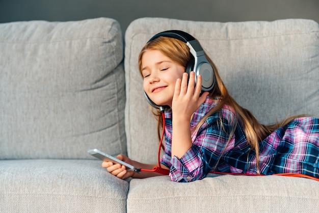 Слушайте музыку дома. красивая маленькая девочка с улыбкой поправляет наушники, лежа на диване у себя дома