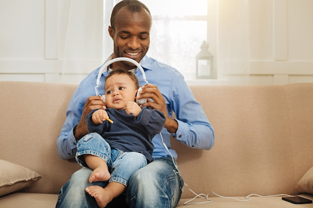 Enjoying music. good-looking gleeful afro-american man holding his little son and putting headphones on him while sitting on the couch