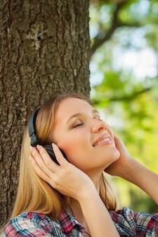 공원에서 음악을 즐긴다. 헤드폰을 끼고 공원에서 나무에 기대어 음악을 듣고 웃고 있는 아름다운 젊은 여성의 측면