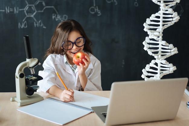Наслаждаюсь своим перерывом. улыбающийся счастливый довольный подросток сидит в лаборатории и наслаждается задачами микробиологии, делая заметки и ест яблоко