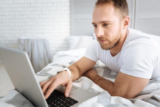 Наслаждаюсь своей работой фрилансером. улыбающийся спортивный очаровательный мужчина, лежащий на кровати и использующий ноутбук, выражая интерес