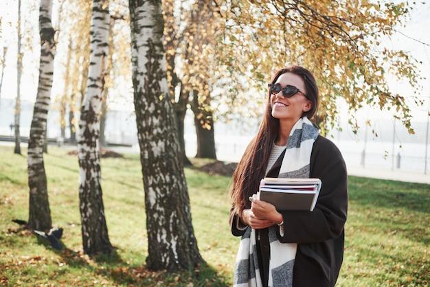 自然と暖かい日を楽しんでいます。サングラスの若い笑顔ブルネットは木の近くの公園に立っているし、メモ帳を保持しています。
