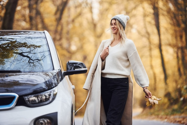 Enjoying nature. girl have autumn trip by car. modern brand new automobile in the forest.