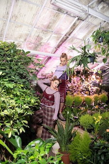 自然を満喫中。温室での時間を楽しみながら、平和な 2 人の素敵な女性のトップ ビュー