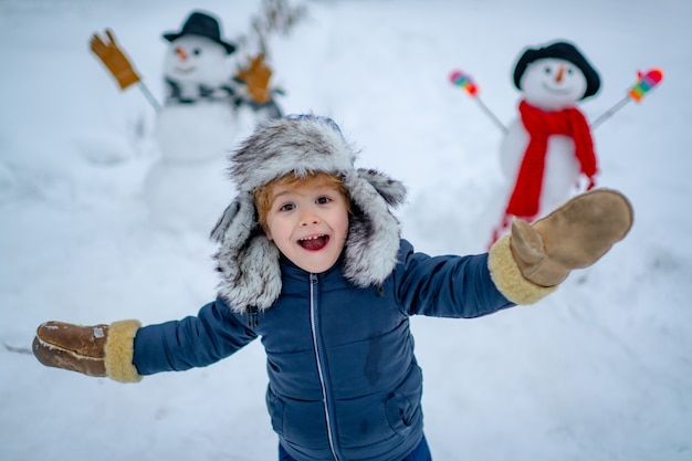 Enjoying nature wintertime winter kid funny boy posing on winter weather snowman and funny little bo...