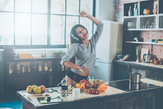 Enjoying new day. beautiful young mixed race woman in headphones cooking salad and dancing while standing in kitchen at home