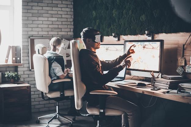 新しい現実を楽しんでいます。バーチャルリアリティヘッドセットを身に着けて、若い女性の近くの創造的なオフィスで彼の机に座って身振りで示すハンサムな若い男