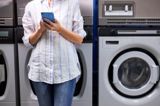 簡単な洗濯工程を楽しんでいます。洗濯機の近くに立ってスマートフォンアプリを見て、洗濯の終わりを待っている若い女性のトリミングされた写真