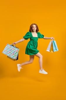 구매의 즐거움. 많은 쇼핑 팩을 들고 점프하는 행복한 빨간 머리 세련된 아가씨. 노란색 배경 위에 격리된 녹색 드레스를 입고 쇼핑을 마치고 집으로 뛰어가는 예쁜 아가씨