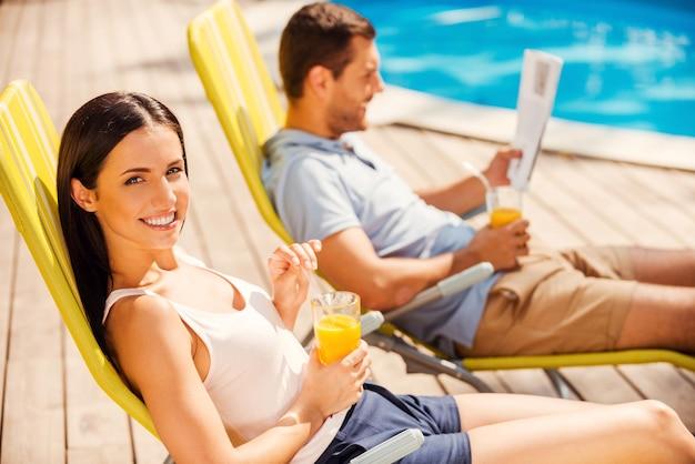 Наслаждаясь апельсиновой свежестью у бассейна. вид сбоку красивой молодой пары, сидящей на шезлонгах у бассейна, пока женщина смотрит в камеру и улыбается
