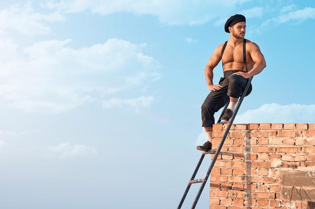 屋外で楽しむ。はしごに座って、背景の青い空を楽しく見つめているセクシーな上半身裸の建設労働者の水平方向のショット