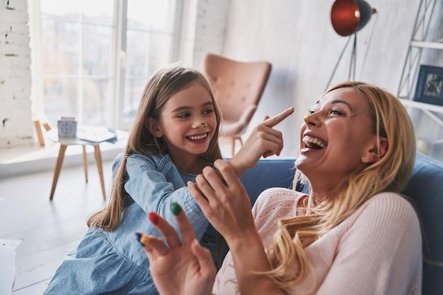 絵を楽しんでいます。家でのんびりとした時間を過ごしながら、若い母親に顔の絵を描いて笑うかわいい女の子