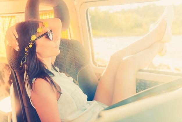 Наслаждаюсь прекрасным днем. красивая молодая женщина расслабляется, сидя на переднем сиденье своего минивэна