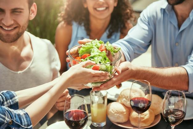 一緒にピクニックを楽しんでいる間、彼女の友人に新鮮なサラダを与える女性のトリミングされた画像
