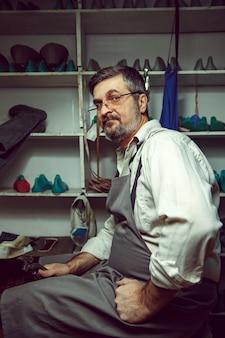 Godendo del processo di creazione di scarpe su misura. luogo di lavoro del designer di scarpe. mani del calzolaio con lo strumento del calzolaio