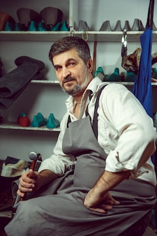 Enjoying process of creation custom made shoes. workplace of shoe designer. hands of shoemaker with cobbler tool
