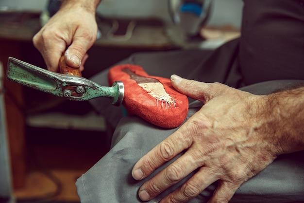 クラフトシューズ作りの工程を楽しんでいます。靴デザイナーの職場。コブラーツールを扱う靴屋の手、クローズアップ