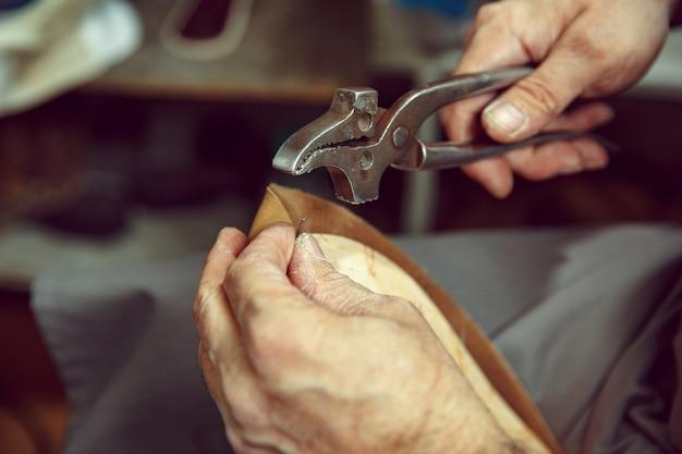 クラフトシューズ作りのプロセスを楽しんでいます。靴デザイナーの職場。コブラーツールを扱う靴屋の手、クローズアップ