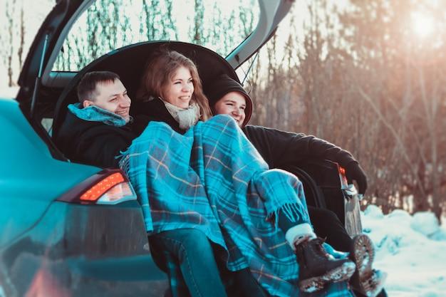 가장 친한 친구와 함께 여행을 즐기고 있습니다. 겨울 숲의 자동차 트렁크에서 도로 여행을 즐기는 젊은 쾌활한 사람들 - 차로 여행