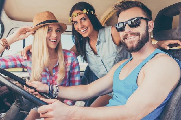 Наслаждаюсь поездкой. две счастливые молодые женщины улыбаются в камеру и сидят внутри минивэна, пока мужчина за рулем