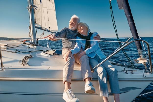 帆船やヨットで抱き締めてリラックスして幸せな素敵なシニア家族のカップルのセーリングを楽しんでいます