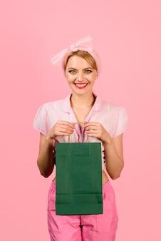ショッピングを楽しむ美しい少女は、ショッピングバッグを手にショッピングバッグスタイリッシュな若い女性を保持します