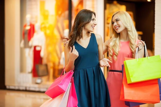 Наслаждаясь покупками. две красивые молодые женщины вместе делают покупки и разговаривают