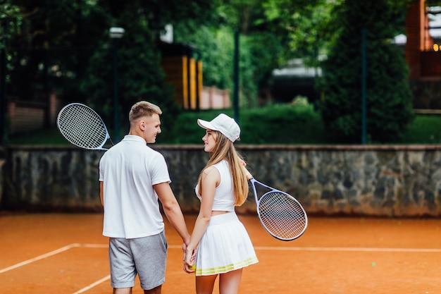 함께 시간을 보내는 것을 즐깁니다. 전체 길이의 등, 아름다운 젊은 부부가 테니스 코트에서 미소로 서로를 바라보고 있습니다.