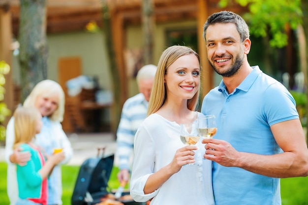 Enjoying summer barbeque with family. happy young couple bonding to each other and holding wine glasses while other members of family barbecuing food in the background