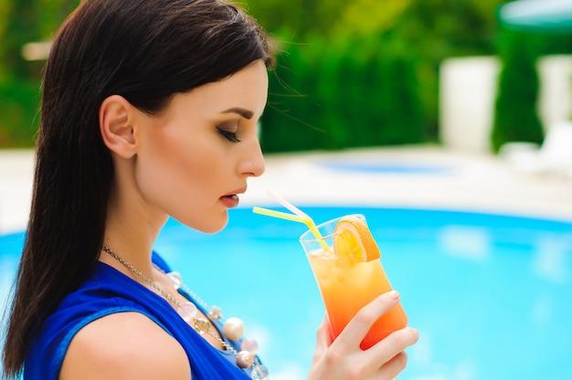 夏を楽しんでいます。プールのそばでリラックスしながらカクテルを飲みながら美しい若い女性。