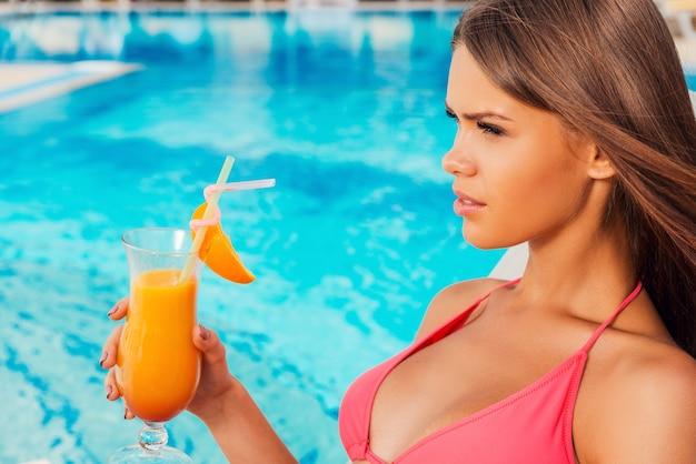 수영장에서 여름을 즐기고 있습니다. 수영장 옆에 앉아 있는 동안 칵테일을 들고 비키니 입은 아름다운 젊은 여성의 측면