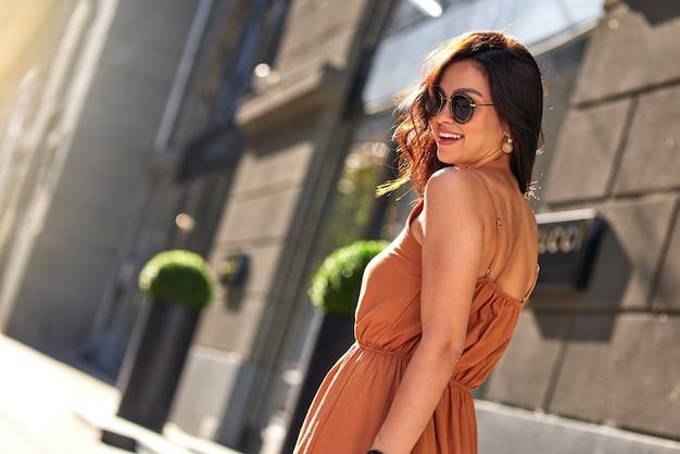 야외에서 여름날을 즐기고 있습니다. 긴 로맨틱 드레스와 안경을 쓰고 도시 거리를 걷는 동안 카메라를 바라보는 젊은 여성의 뒷모습. 사람들의 라이프 스타일과 패션 개념