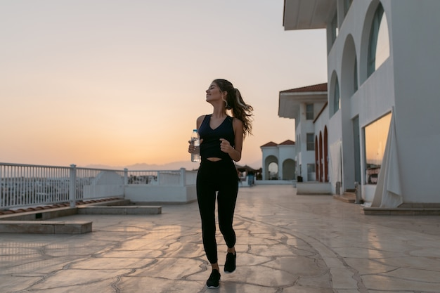 Godendo di mattina di sole estivo sul lungomare di bella giovane donna sportiva in esecuzione con bottiglia d'acqua. sorridere a lato con gli occhi chiusi, paese tropicale orientale, allenamento, allenamento fuori