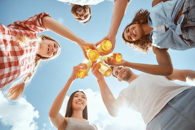夏を楽しんでいる幸せな若者たちは、ビールでボトルをチリンと鳴らし、青に対して微笑んでいます