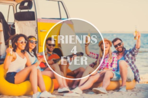一緒に夏の時間を楽しんでいます。彼らのレトロなバンの近くのビーチに座って一緒に楽しんで幸せな若者のグループ