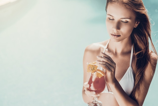 Enjoying summertime. beautiful young woman in white bikini holding cocktail and keeping eyes closed while relaxing poolside