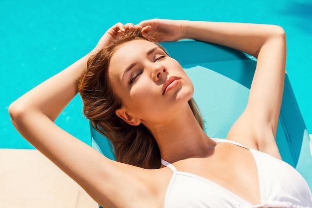 プールサイドで夏を楽しんでいます。プールの近くのデッキチェアでリラックスした白いビキニの美しい若い女性の上面図