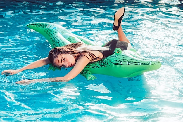 Enjoying suntan and vacation. colorful portrait of pretty young woman in black swimsuit lying on green inflatable mattres at swimming pool