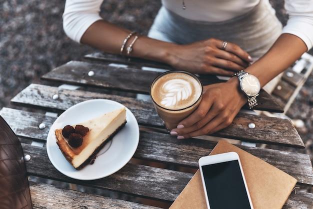 Наслаждаемся вкусным обедом. крупным планом вид сверху молодой женщины, держащей чашку кофе, сидя в ресторане на открытом воздухе