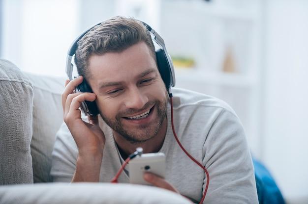 その歌を楽しんでいます。音楽を聴いてヘッドフォンでハンサムな若い笑顔の男